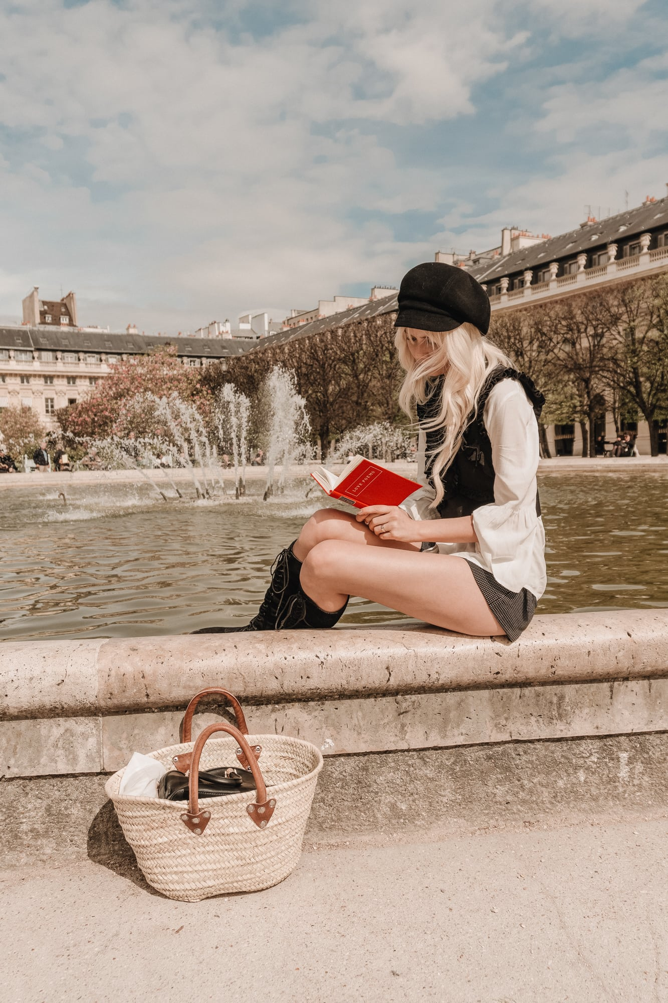 Sarah Loven reading by fountain, Palais Royal Paris