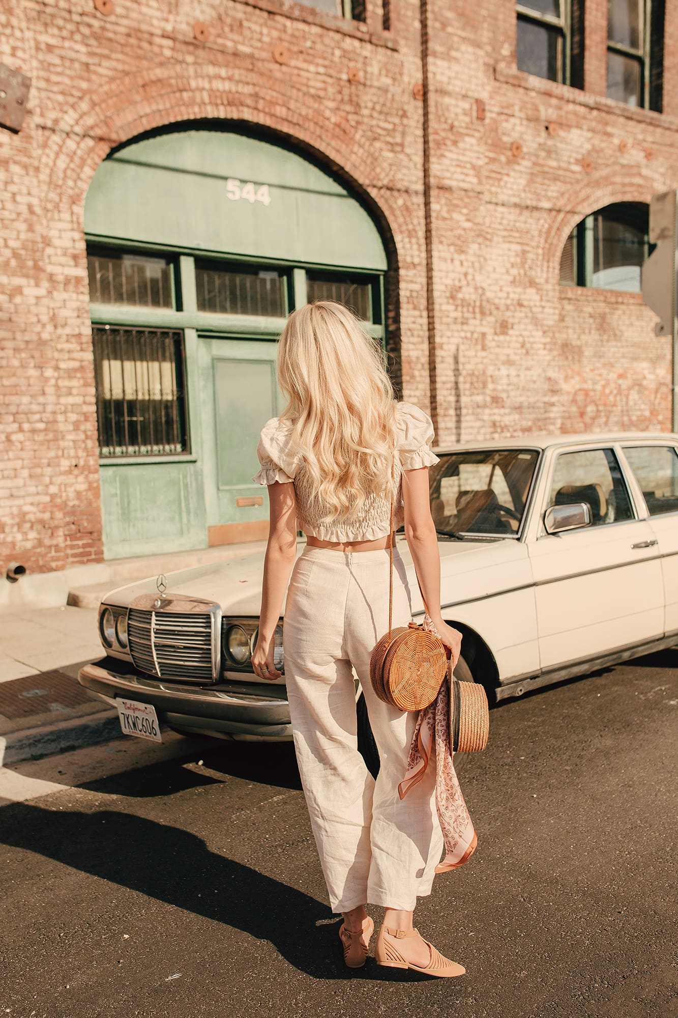 Blonde girl wearing vintage outfit in downtown LA next to vintage car